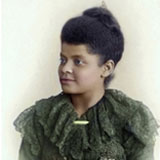 Hand painted photograph of an attractive African American woman. She is wearing a green dress with ruffles. Her hair is natural and pulled up into a bun.
