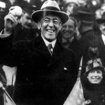 President Woodrow Wilson holding a baseball in a crowd filled outdoor stadium.