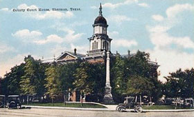Vintage postcard showiing red brick courthouse, blue sky with cumulus clouds.